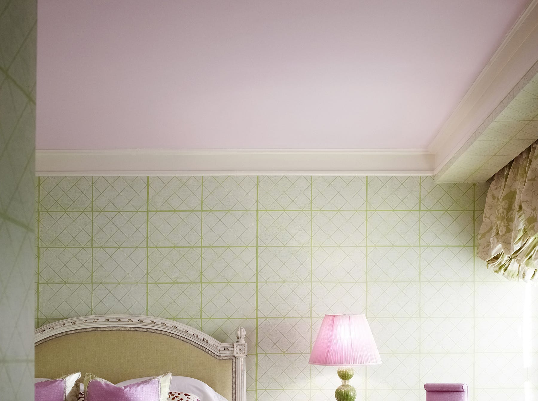 Offsetting a hand-blocked wallpaper in light spring green, Jamie Drake chose to pull out pinks from the rug and fabrics, with a ceiling painted in a soft shade of boysenberry mousse.