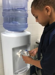 A student from Schulze Elementary School in Detroit stops for a drink of water in the hallway on the first day of school on Tuesday.