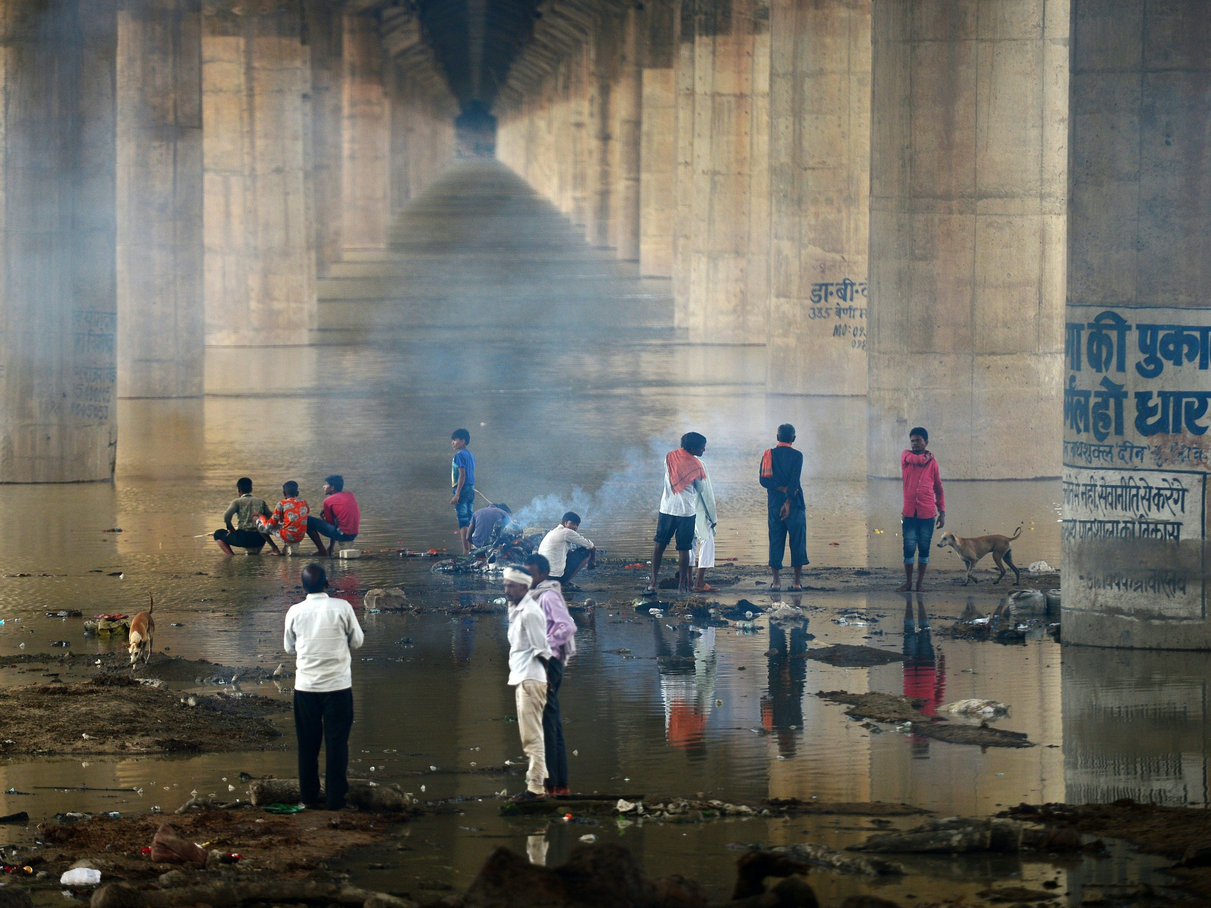Indian people cremate a body near the flooded River Ganges under Shastri bridge at Daraganj ghat, in Allahabad on September 3, 2018, as water levels of the Ganges and Yamuna rivers increase following monsoon rains.