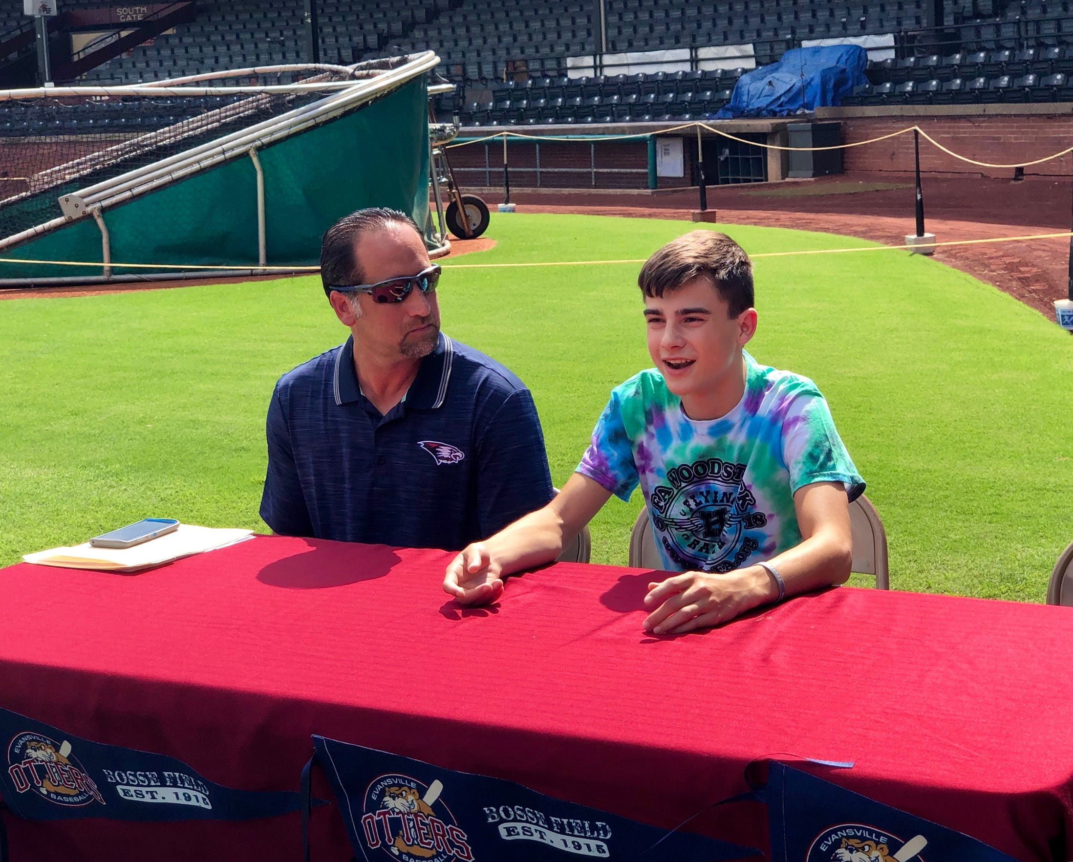 USI baseball coach Tracy Archuleta sits with his son Sam during a news conference last month at Bosse Field.