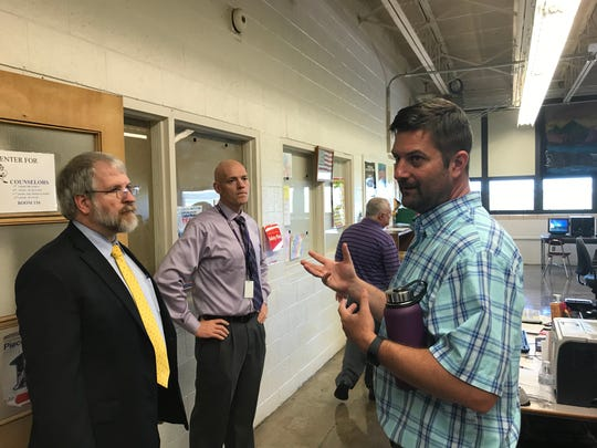 Personalized Learning Center instructor John Cahill, right, speaks to Ohio Department of Education Superintendent Paolo DeMaria, left, and Ross High School Principal Brian Zeller, middle, about the new online learning lab.
