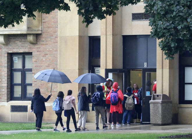 Washington Middle School staff greet students and provide shelter for the rain as children arrived for the first day of school Tuesday in Green Bay.