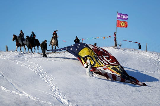 """FILE - in this Dec. 4, 2016, file photo, veterans unveil a banner that reads """"One Water"""" on a hillside across from the Oceti Sakowin camp where people have gathered to protest the Dakota Access oil pipeline in Cannon Ball, N.D.  Civil liberties advocates have sued the U.S government alleging law enforcement agencies are maneuvering to crack down on anticipated protests over the Keystone XL oil pipeline. The suit cites prior efforts to disband protesters opposed to a separate project, the Dakota Access Pipeline. (AP Photo/David Goldman, File)"""