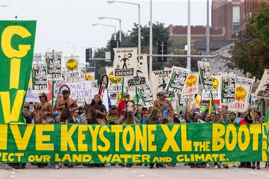 FILE - In this Aug. 6, 2017, file photo, demonstrators against the Keystone XL pipeline march in Lincoln, Neb. Civil liberties advocates have sued the U.S government alleging law enforcement agencies are maneuvering to crack down on anticipated protests over the Keystone XL oil pipeline. Attorneys for the American Civil Liberties Union want the court to order the release of all records pertaining to cooperation between federal, state and local law enforcement and private security companies. The suit cites prior efforts to disband protesters opposed to a separate project, the Dakota Access Pipeline. (AP Photo/Nati Harnik, file)
