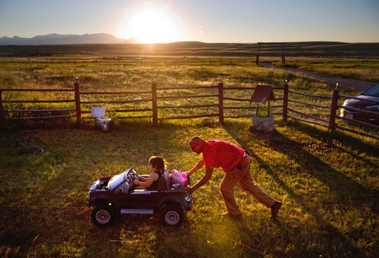 Randy Ortiz, right, pushes Ronnie Loring, 3, the cousin of Ashley HeavyRunner Loring, as they take a break from searching for her. The family has logged about 40 searches but there's no way to cover a 1.5 million acre reservation, an expanse larger than Delaware.