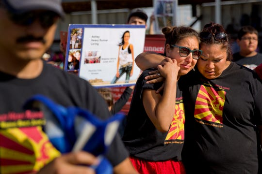 Jenna Loring, left, the aunt of Ashley HeavyRunner Loring, cries with her cousin, Lissa Loring, during a traditional blanket dance before the crowd at the North American Indian Days celebration in July.