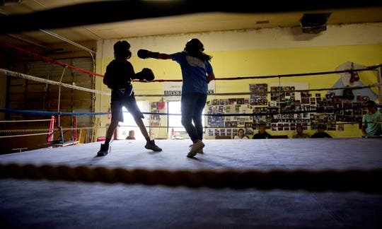 """ADVANCE FOR USE WEDNESDAY, SEPT. 5, 2018 AND THEREAFTER-Beatrice Kipp, 13, right, spars with Timmy Sellars, 14, at the Blackfeet Native Boxing Club on the Blackfeet Indian Reservation in Browning, Mont., Saturday, July 14, 2018. """"I'm protective of our children because of human trafficking. What happened to Ashley is really worrying,"""" said Frank Kipp who teaches his daughters how to box and runs the club. """"We teach our girls if someone grabs you, you fight to your death."""" (AP Photo/David Goldman)"""