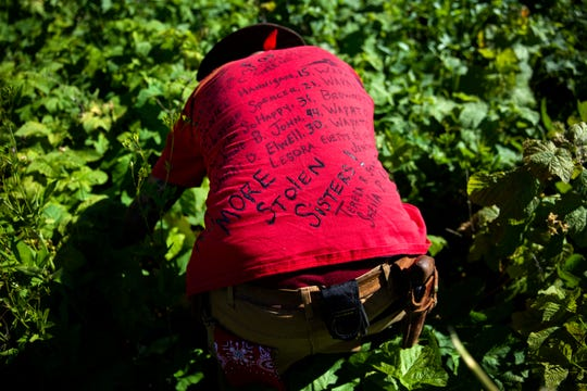 Randy Ortiz wears a shirt with the names of missing and murdered indigenous women as he searches for Ashley HeavyRunner Loring in the mountains of the Blackfeet Indian Reservation in Babb.
