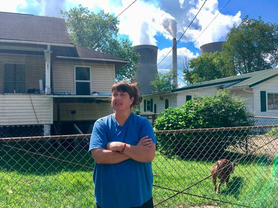 In this Aug. 23, 2018 photo, Andrea Maxey of Poca, W.Va., speaks outside her home with the American Electric Power's John Amos coal-fired power plant is in the background across the Kanawha River in Winfield. Maxey says emissions from the plant aren't a nuisance.  President Donald Trump picked West Virginia where he announced rolling back pollution rules for coal-fired power plants. But he didn't mention that the northern two-thirds of West Virginia, with the neighboring part of Pennsylvania, would be hit hardest.  (AP Photo/John Raby)