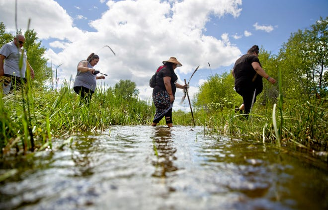 Kimberly Loring, from right, Roxanne White, Lissa Loring and George A. Hall, cross a creek looking for clues during a search for the Lorings' sister and cousin, Ashley HeavyRunner Loring, who went missing in 2017 from the Blackfeet Indian Reservation.