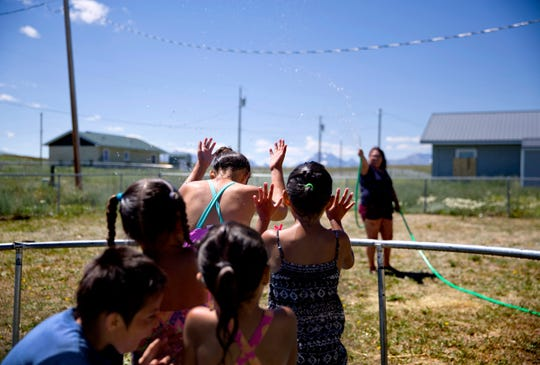 Tyisha ArrowTop Knot, right, sprays her nieces and nephews with a garden hose while looking after them in the backyard of their home in Browning,.
