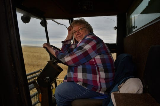 Myrna Paulus monitors the grain pouring from her combine's boom into the bed of a grain truck driven by her son Nate, Thursday, August 30, 2018.