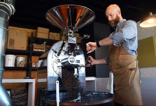 Tommy Teepell, owner of Grin Coffee, times his roasted coffee beans at his shop each morning.