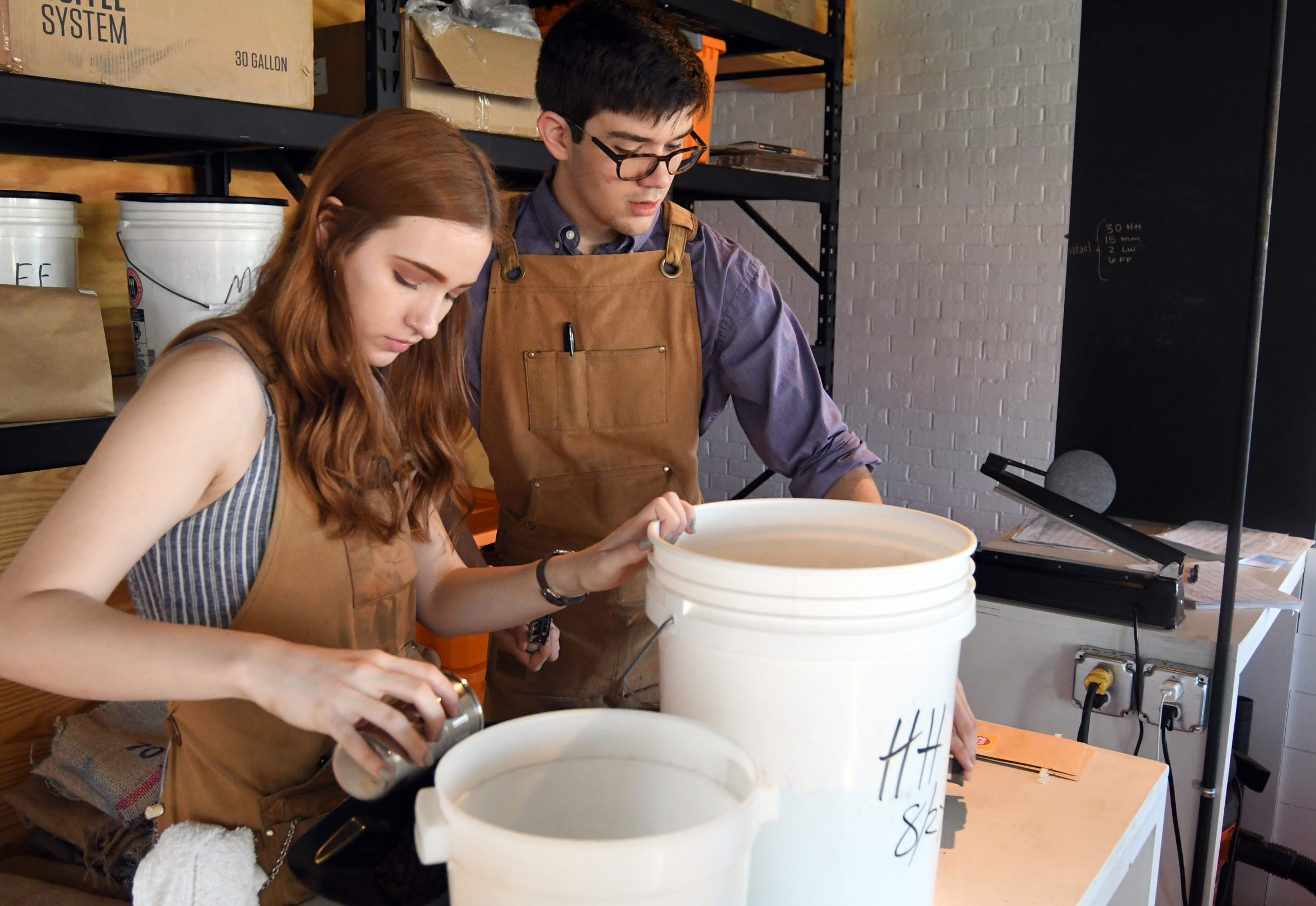 Employees Mikayla Hollingsworth and Micah Graves pour coffee beans into individual bags at Grin Coffee in Hattiesburg.