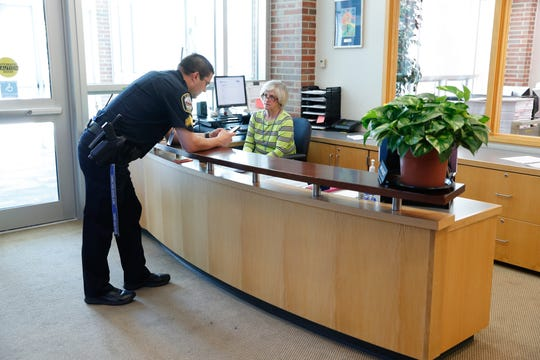 Carmel Clay SchoolsÊResource Officer, Sgt. D.J. Schoeff chats with Front office Administrative Assistant M.J. Schloot about a visitor's badge at  Carmel High School in Carmel Ind. on Thursday, Aug. 30, 2018.