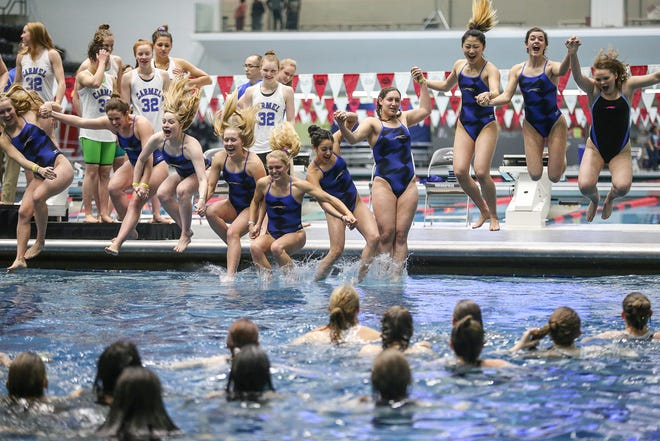 Carmel swimmers jump into the pool, a tradition after each of their 32 consecutive state titles, at IHSAA girls state swimming finals at IUPUI Natatorium in Indianapolis, Saturday, Feb. 10, 2018. The state title winning streak holds a national record.