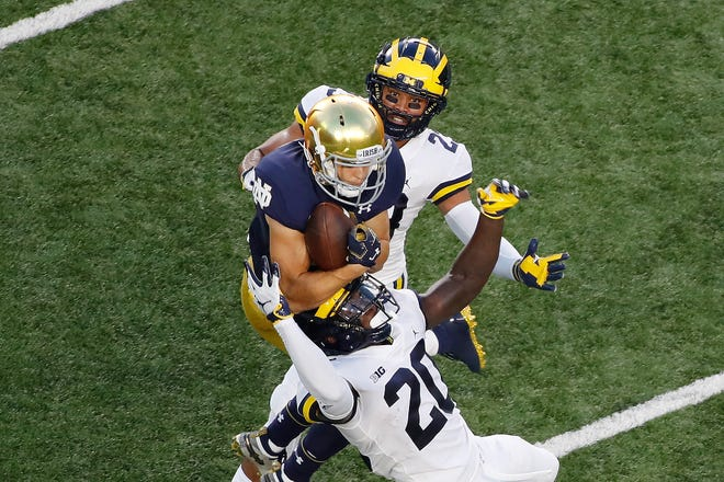Fighting Irish wide receiver Chris Finke (10) catches a pass in the end zone for a touchdown against Michigan Wolverines defensive backs Jared Davis (23) and Brad Hawkins (20) during the first quarter at Notre Dame Stadium.