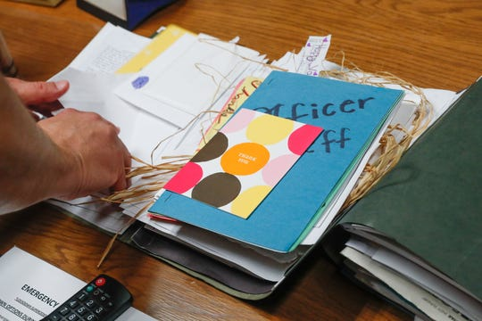 A folder containing almost a decade with of thank you cards, and letters from former students is opened by Carmel Clay SchoolsÊResource Officer, Sgt. D.J. Schoeff, at Carmel High School in Carmel Ind. on Thursday, Aug. 30, 2018.