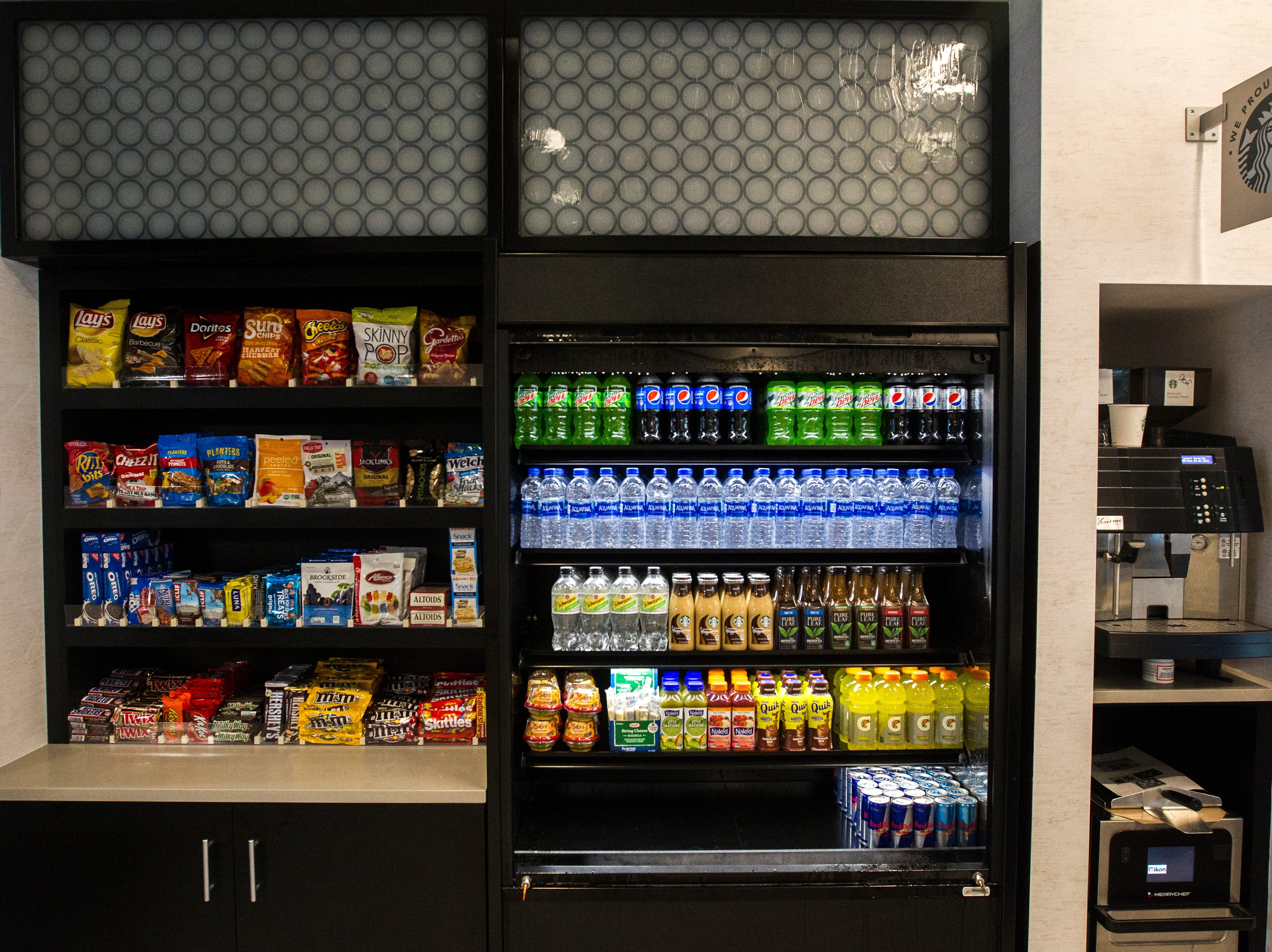 Display cases are stocked full next to the first floor bar during a tour on Tuesday, Sept. 4, 2018, at Hyatt Place on the corner of Court and Linn Streets in downtown Iowa City.