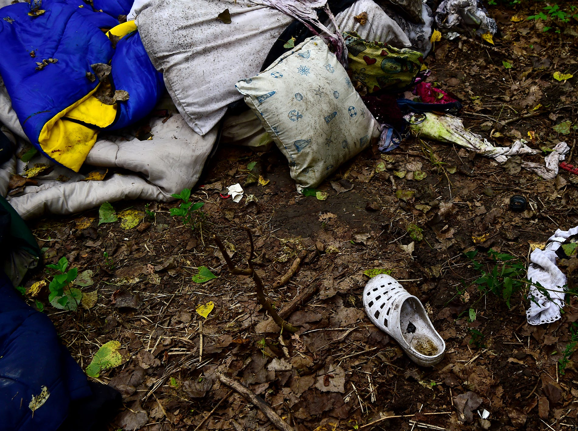 Shoes, pillows and clothes are among the belongings strewn in The Jungle in Ithaca, August 31, 2018. Located behind the shopping centers along Rt. 13, The Jungle is home to dozens of homeless people who live in tents and makeshift shacks.