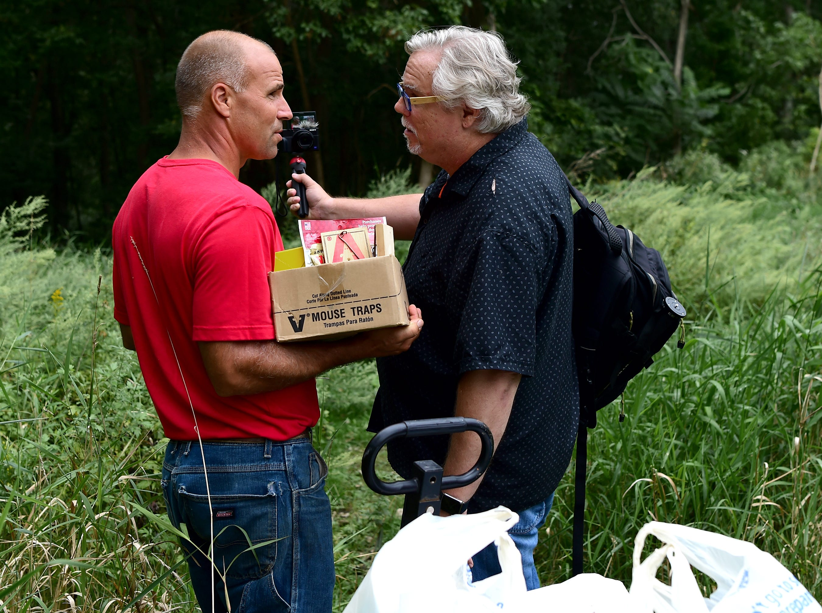 """Carmen Guidi of Newfield, right, is interviewed by Mark Horvath, left, as they deliver supplies to residents of """"The Jungle"""" in Ithaca on August 31, 2018. Horvath is the founder of Invisible People, which brings attention to homelessness worldwide."""
