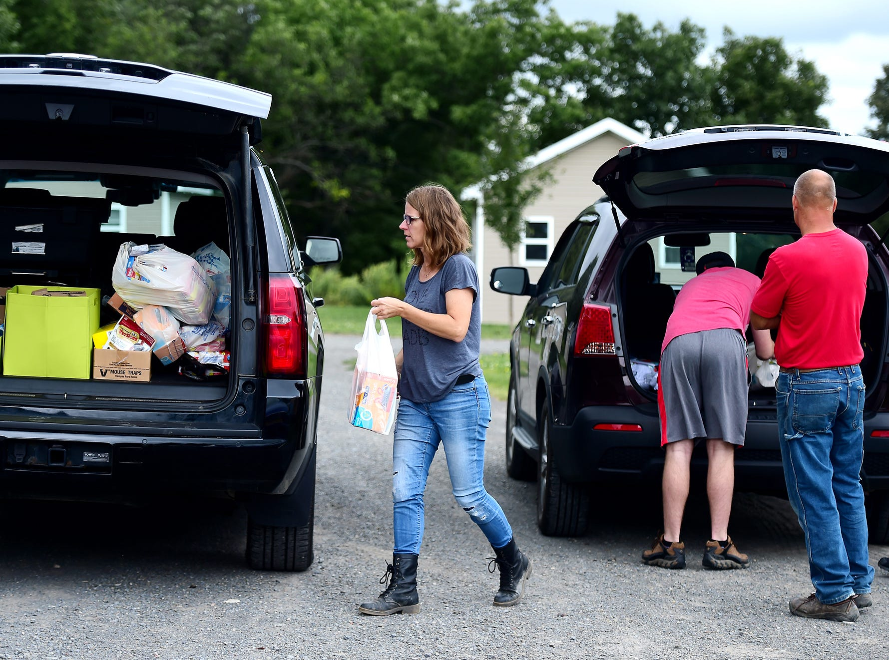 """Deb Wilke of Horseheads loads supplies into her car which she will deliver to residents of """"The Jungle"""" in Ithaca on August 31, 2018. Wilke, along with her husband and four children, help the homeless residents of The Jungle by delivering food and supplies, providing rides, taking residents out to dinner and to do laundry, and helping them find permanent housing."""