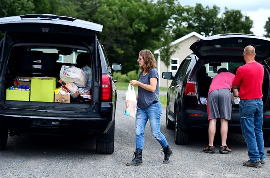 "Deb Wilke of Horseheads loads supplies into her car which she will deliver to residents of ""The Jungle"" in Ithaca on August 31, 2018. Wilke, along with her husband and four children, help the homeless residents of The Jungle by delivering food and supplies, providing rides, taking residents out to dinner and to do laundry, and helping them find permanent housing."