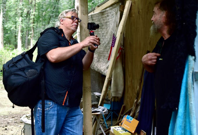Mark Horvath, left, interviews Bill, who lives in The Jungle in Ithaca, on August 31, 2018. Horvath is the founder of Invisible People, an organization which seeks to raise awareness by letting homeless people worldwide by empowering them to share their stories.