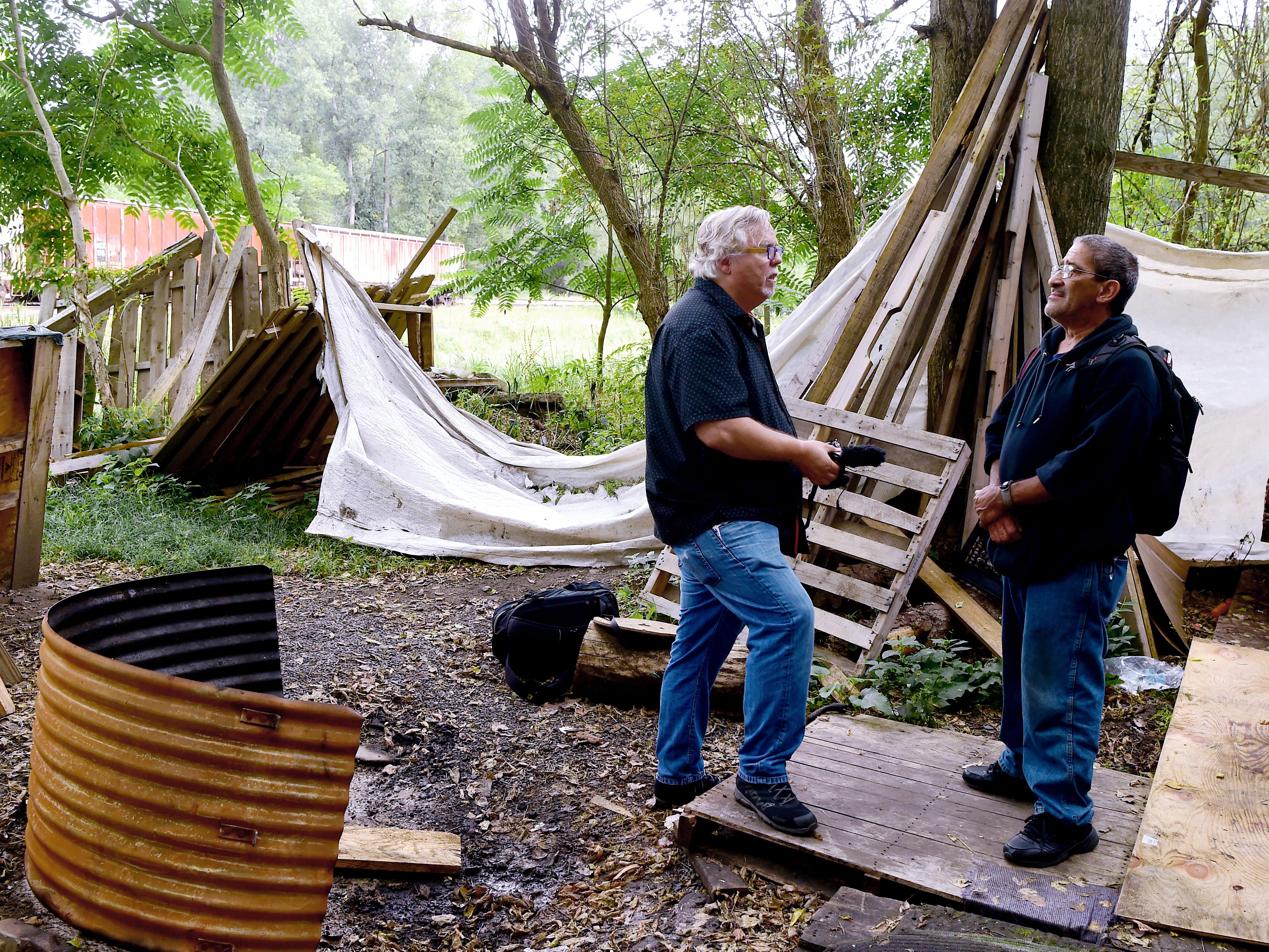 """Mark Horvath talks to Sinbad on August 31, 2018, in Ithaca's homeless encampment, """"The Jungle."""" Horvath, of Binghamton, is the founder of Invisible People, and travels worldwide to help raise awareness about homelessness."""