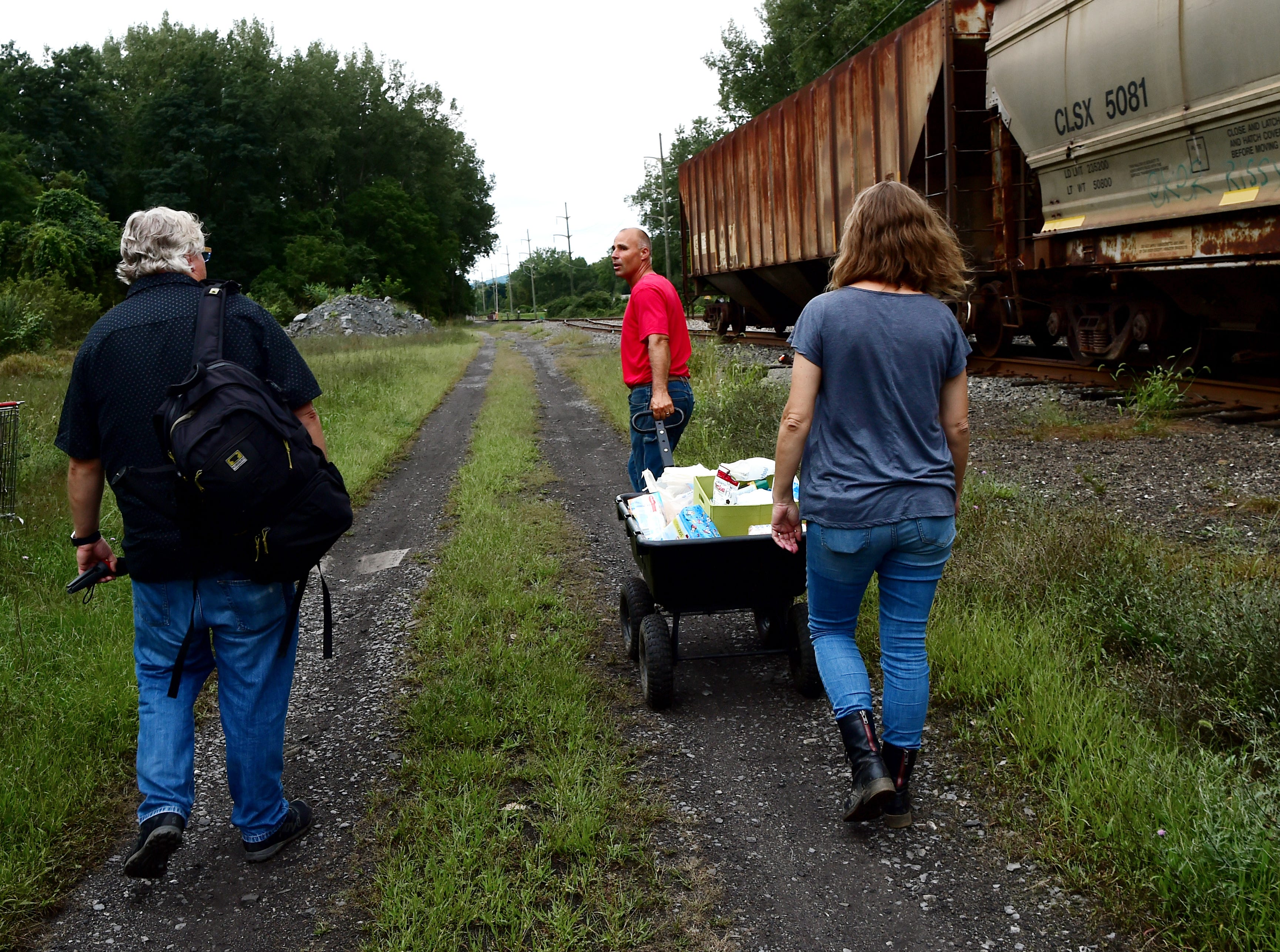 Mark Horvath of Binghamton, Carmen Guidi of Newfield,  and Deb Wilke of Horseheads, deliver essential supplies including water, toilet paper and bug repellant, to The Jungle in Ithaca on August 31, 2018. Located behind the shopping centers along Rt. 13, The Jungle is home to dozens of homeless people.