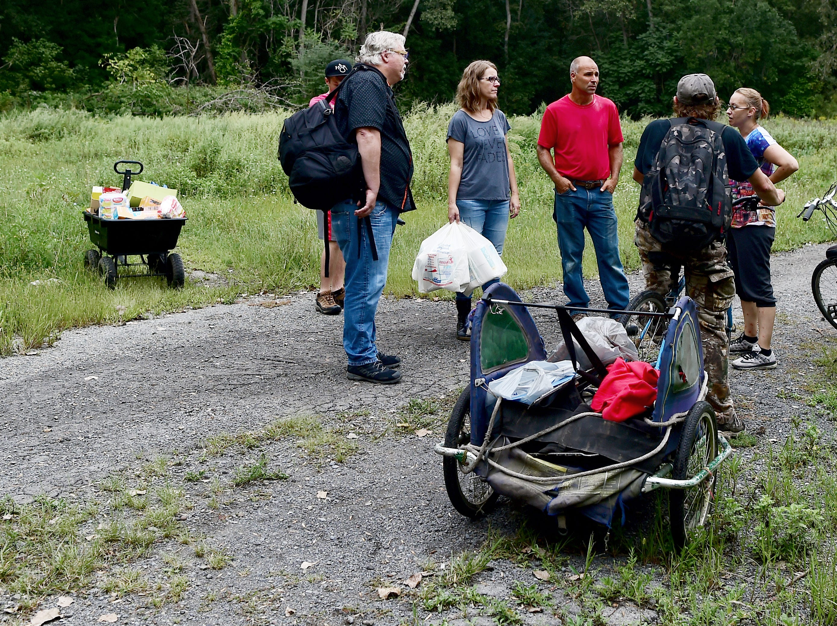 """Mark Horvath of Binghamton, Noah and Deb Wilke of Horseheads, and Carmen Guidi of Newfield, deliver essential supplies including water, toilet paper and bug repellant, to """"The Jungle"""" in Ithaca on August 31, 2018. Located behind the shopping centers along Rt. 13, The Jungle is home to dozens of homeless people."""