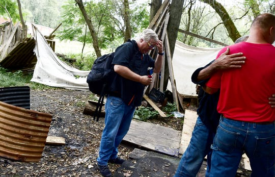 """Mark Horvath takes a moment after interviewing a resident of Ithaca's homeless encampment, """"The Jungle."""" Horvath, of Binghamton, is the founder of Invisible People, and travels worldwide to help raise awareness about homelessness."""