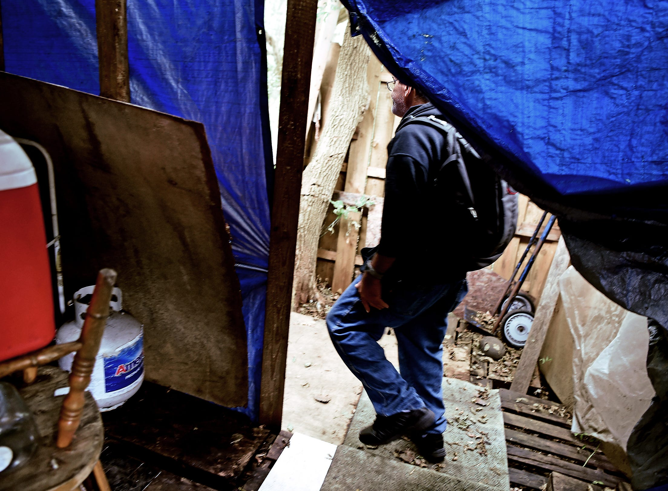 """Sinbad walks through the tarp which serves as the doorway into his home in """"The Jungle"""" in Ithaca on August 31, 2018."""