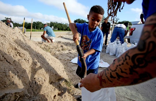 Kamdn Boose, 4, helps his family fill sandbags at Long Beach Harbor, Tuesday, Sept. 4, 2018, in Long Beach, Miss., in advance of Tropical Storm Gordon, which is continuing to strengthen and is expected to become a hurricane late Tuesday when it hits the central U.S. Gulf Coast, including coastal Mississippi.