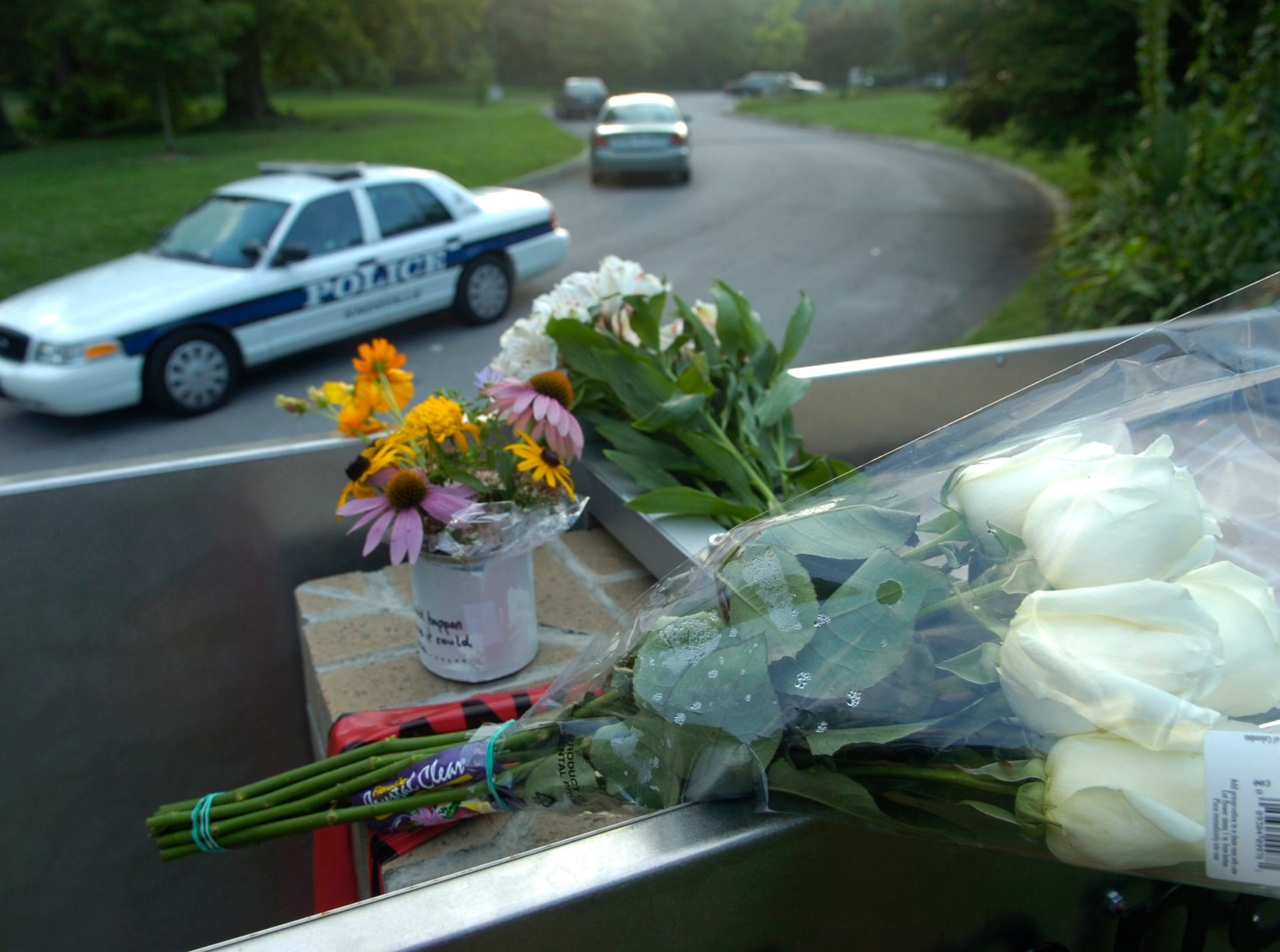 A make-shift memorial of flowers and cards lay on the front sign of the Tennessee Valley Unitarian Universalist Church on Kingston Pike, Sunday, July 27, 2008, as a Knoxville Police Department cruiser guards the entrance to the church. Two people died and several were injured following a shooting Sunday morning during a children's play.
