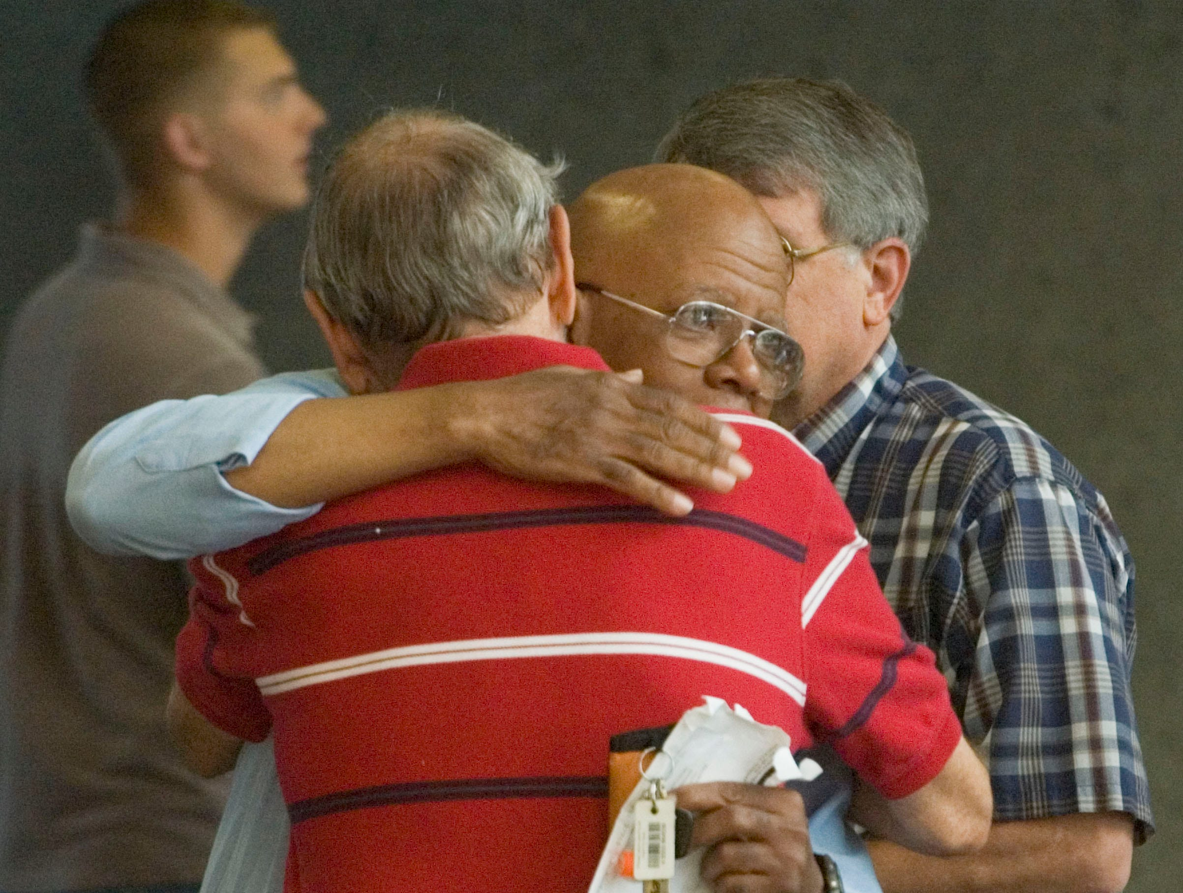 Carl Buice, back to camera, father of Rev. Chris Buice from Tennessee Valley Unitarian Universalist Church, hugs church member Arthur Bolds after a preliminary hearing for the alleged church gunman Wednesday in Knox County General Sessions Court.  Jim David Adkisson, 58, made his first court appearance in connection with the July 27 fatal shooting at Tennessee Valley Unitarian Universalist Church.