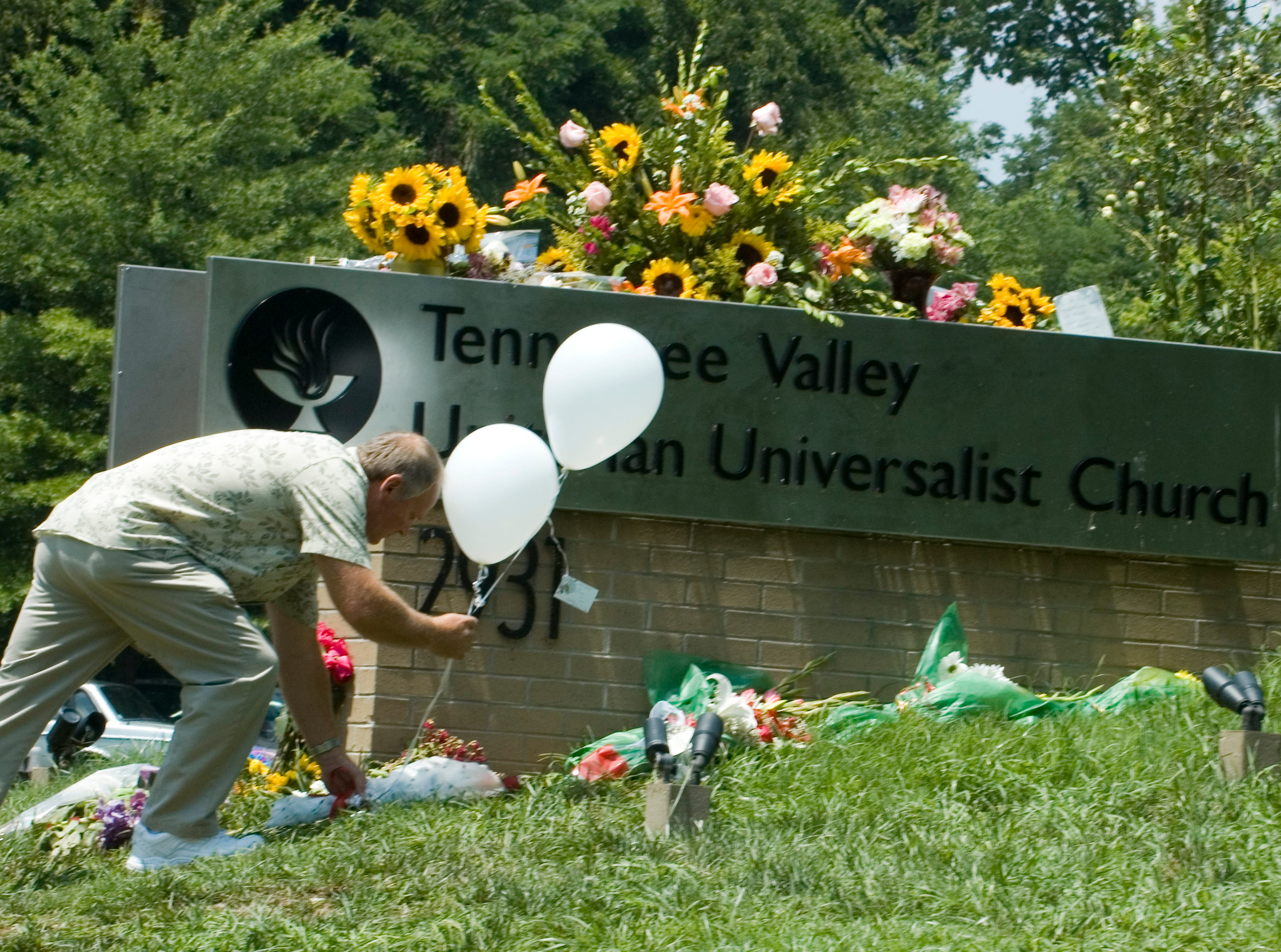 Tom McCosh from the Lighthouse Christian Fellowship in Madisonville, Tn. places of bouquet of eight roses and two white balloons that represent the church members killed and injured in the Sunday shooting at the Tennessee Valley Unitarian Universalist Church.