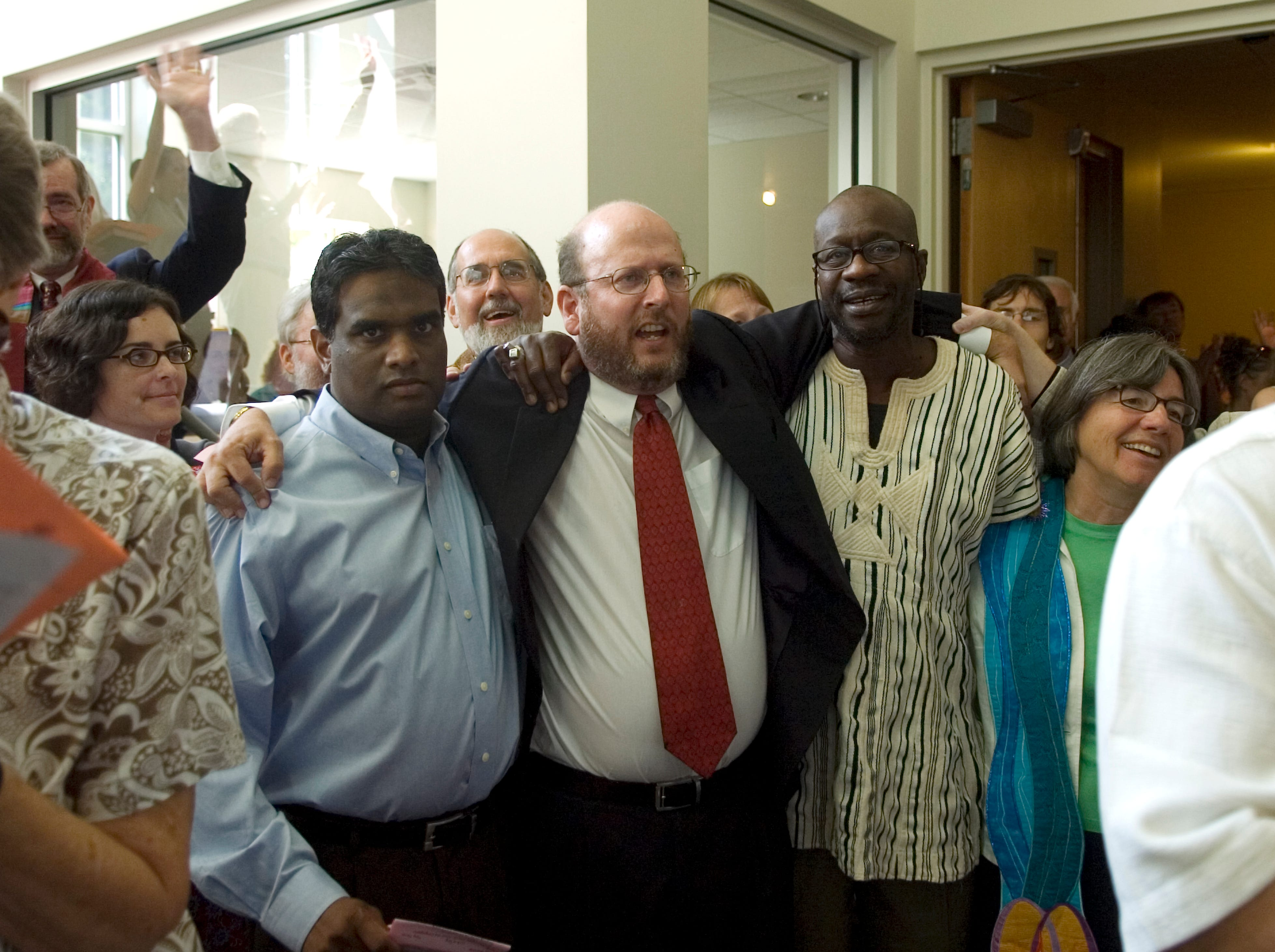"Rev. Chris Buice, center, arm-in-arm with Nathan Paki, left, and Amadou Sall, sing ""Tomorrow"" during the closing of the sanctuary rededication services at the Tennessee Valley Unitarian Universalist Church. ""Tomorrow"" is the song from ""Annie, Jr."" the play being performed last Sunday when a gunman entered the sanctuary and fired a shotgun into the congregation."