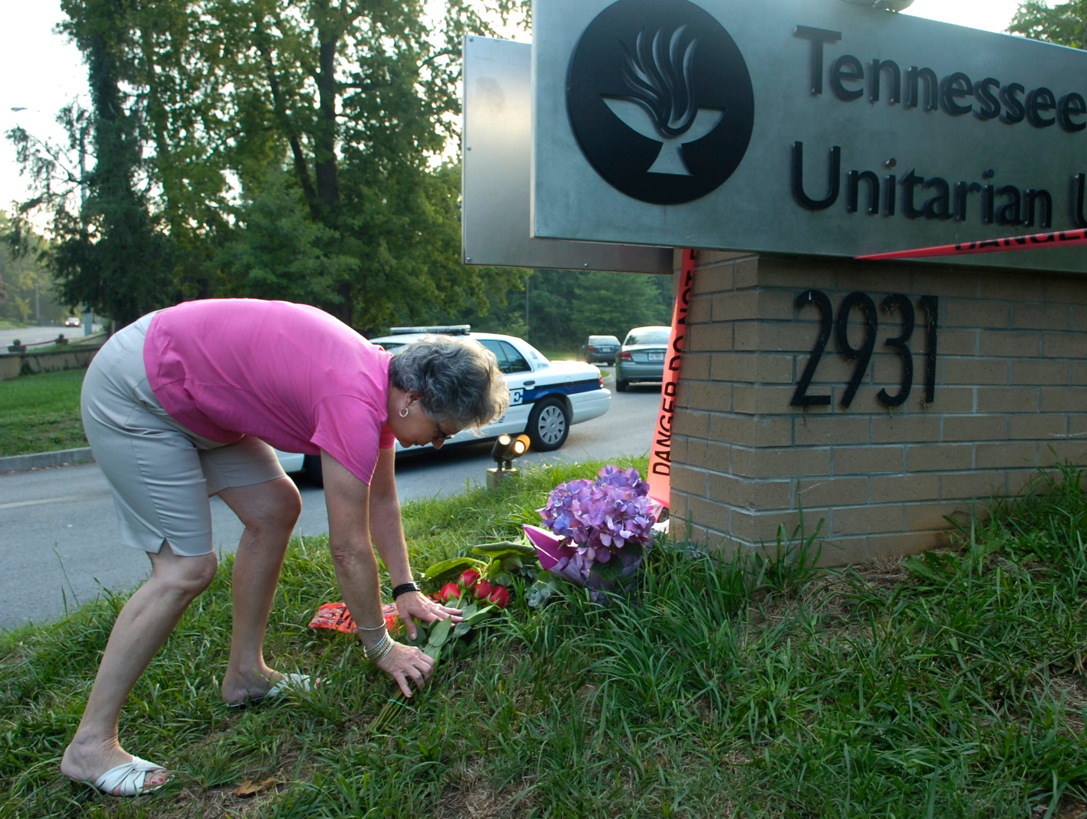 Anna Fraser of Knoxville lays flowers near the front driveway of the Tennessee Valley Unitarian Universalist Church on Kingston Pike where two people died and several were injured following a shooting Sunday morning during a children's play.
