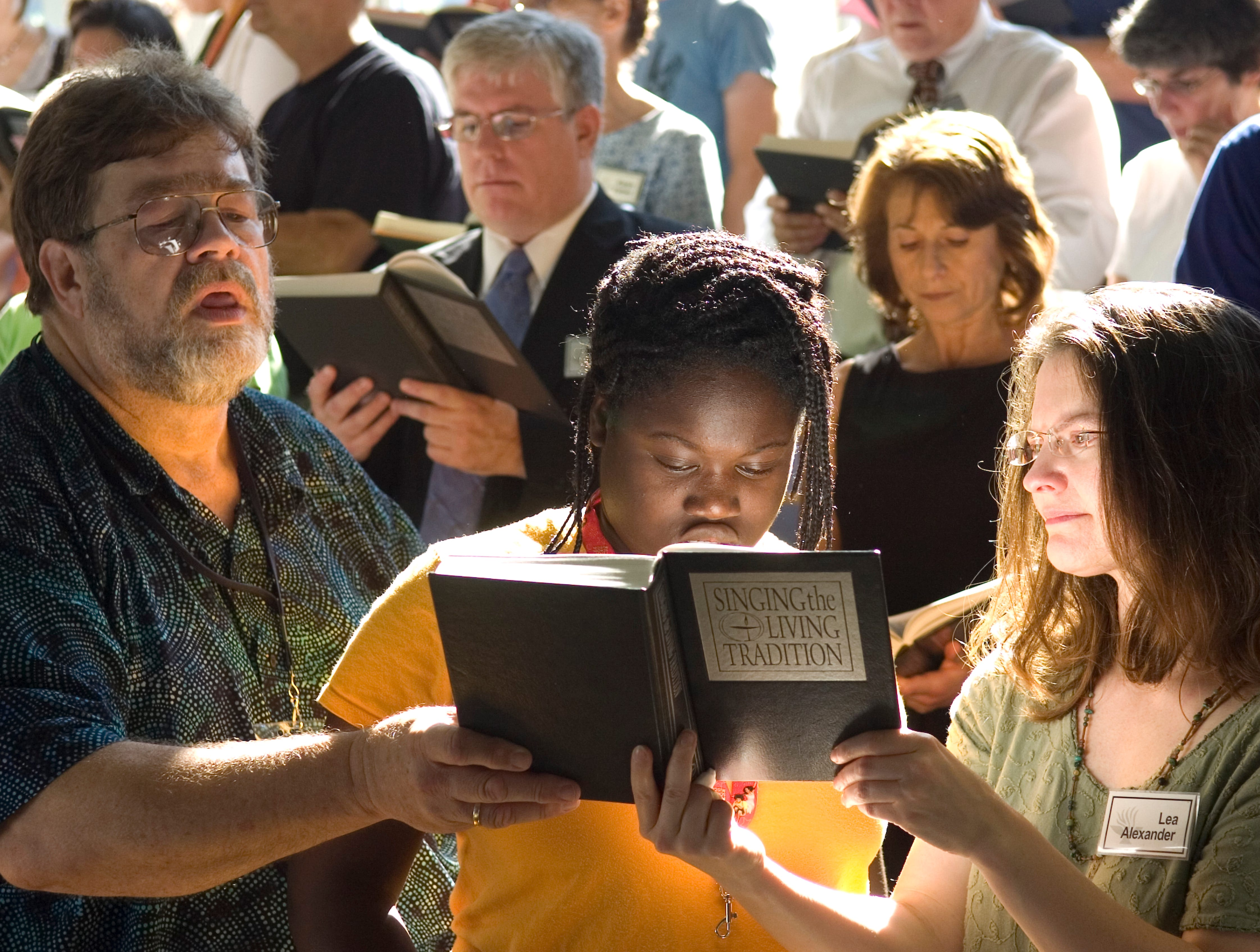 Haley Dockery, 14, center, sings from a hymnal held by her father Bill Dockery, left, with church member Lea Alexander Sunday during the sanctuary rededication services at the Tennessee Valley Unitarian Universalist Church where one week ago a gunman pulled a 12-gauge sawed-off shotgun from a guitar case and fired into the congregation.