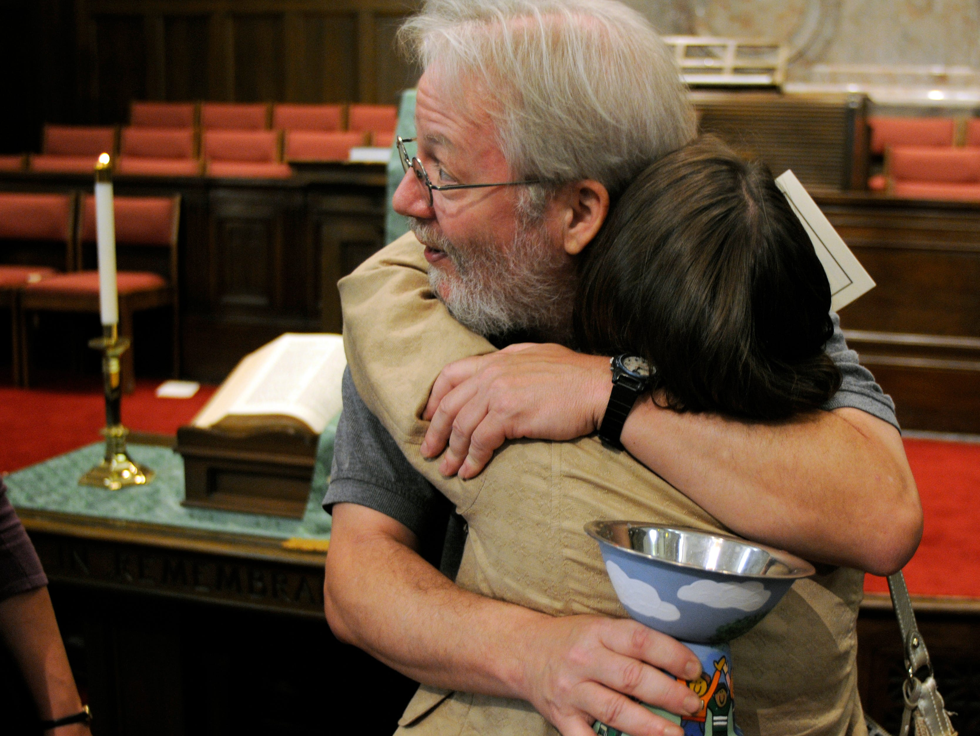 Brian Griffin, director of religious education at Tennessee Valley Unitarian Universalist Church, hugs one of the people who attended a Service of Worship and Hope held at noon Tuesday at First Baptist Church downtown. Griffin is holding a chalice and a candle which he lit for the children during the service.