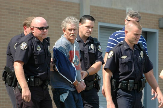 Knoxville Police Department officers leading Jim D. Adkisson, 58, to a squad car in Knoxville, Tenn. Adkisson was charged with the shooting that left two dead and six injured at Tennessee Valley Unitarian Universalist Church. The church shooting was voted the No. 8 news story in Tennessee in 2008..