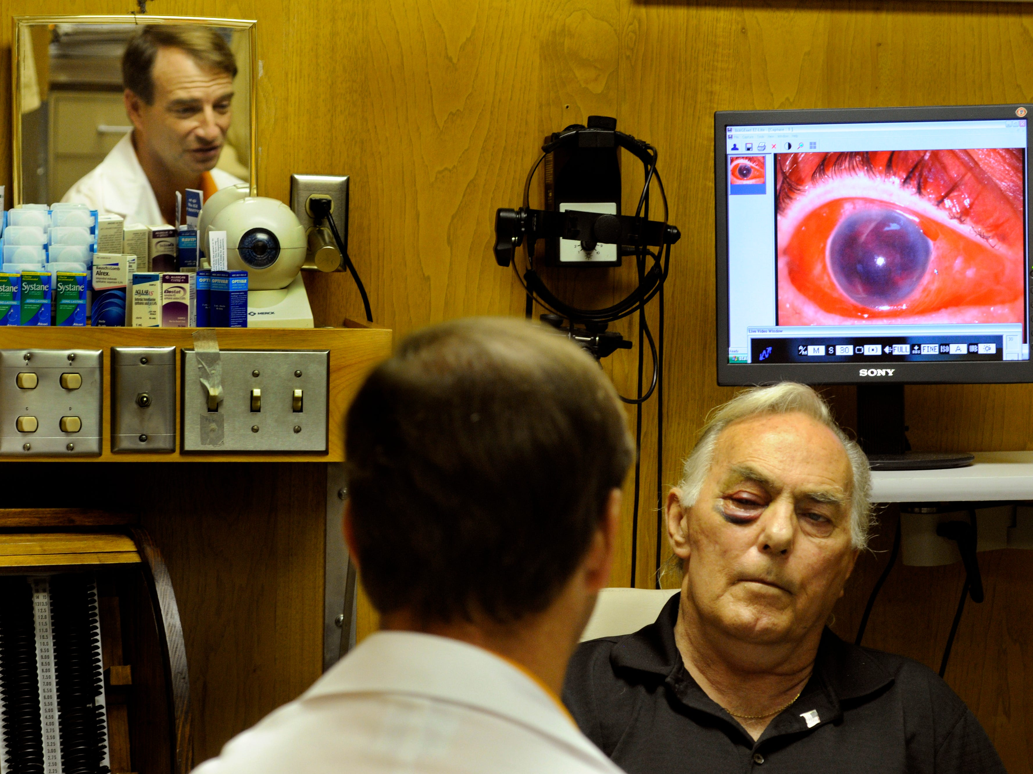 Church shooting victim John T. Worth, right, has his wounded eye examined by Dr. David Harris, Jr., Wednesday at UT Professional Building. Worth, one of the victims at Tennessee Valley Unitarian Universalist Church, had a shotgun pellet strike his right eye. Harris told Worth that it was very unlikely he would regain use of the eye.