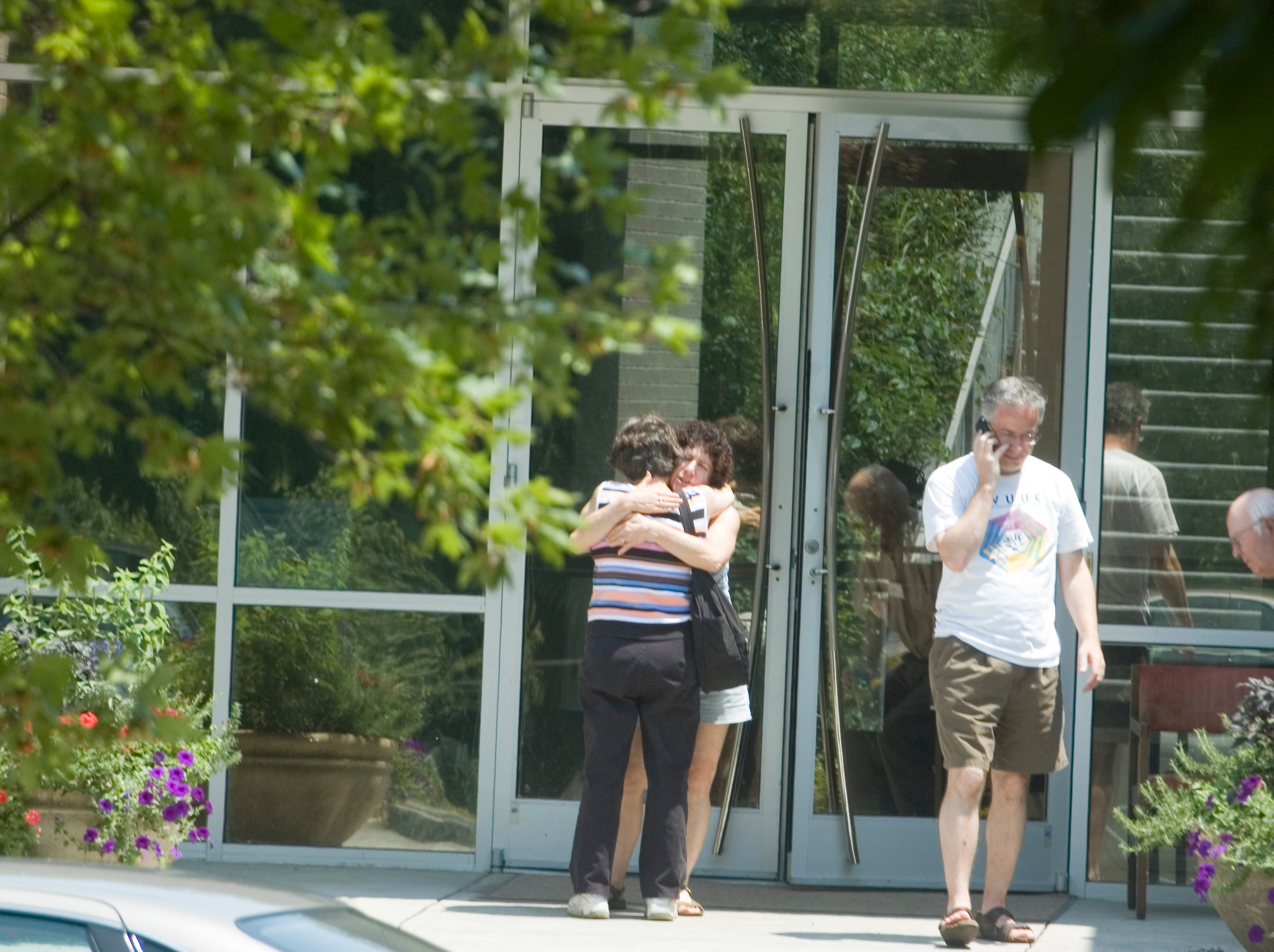 Church members hug outside the entrance to the Tennessee Valley Unitarian Universalist Church Monday, July 28, 2008.