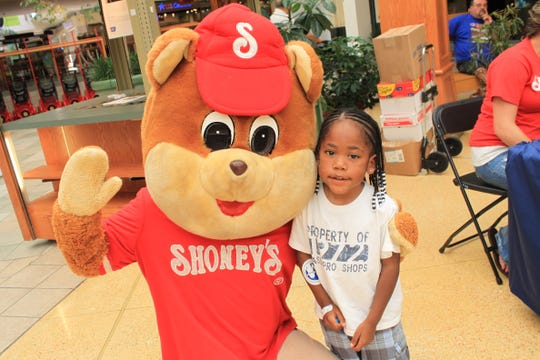 Tywan Taylor gets a hug from the Shoney's bear at the Shoney's Kid Care photo ID event on Friday, August 27.