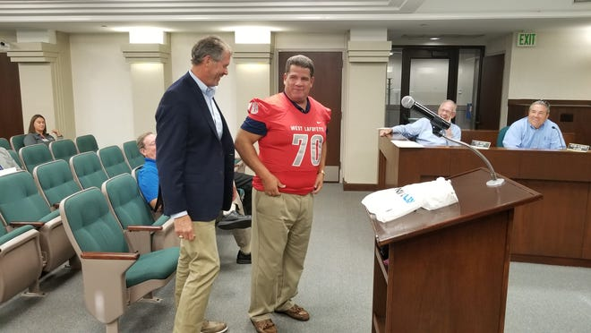 West Lafayette Mayor John Dennis (left) looks as Lafayette Mayor Tony Roswarski (center) puts on a West Lafayette Red Devils' jersey.