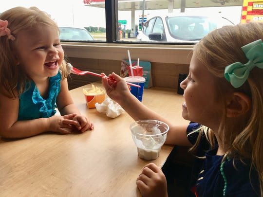 Avery Guidry feeds sister Marie a bite of ice cream at Dairy Queen in Welsh, a town along the Flyway Byway that takes visitors through Jeff Davis Parish.