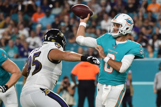 Miami Dolphins quarterback Brock Osweiler attempts a pass under pressure from Baltimore Ravens defensive end Zach Sieler of Pinckney.