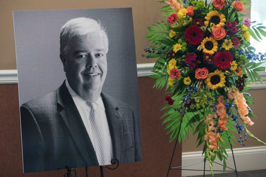 A portrait of John Asher sits with flowers during a public visitation in the Triple Crown Room at Churchill Downs on Tuesday. Sept. 4, 2018