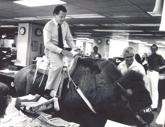 City editor Bill Cox rides a buffalo through the newsroom, 1983